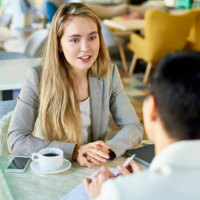 Portrait of two modern young women discussing work sitting at table in cafe during business meeting or job interview